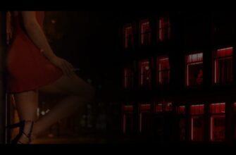 с лева женщина в красном, с права улица с красным свечением из окон