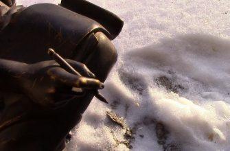 """Рука с пишущим инструментом медной статуи """"Хрисипп"""" на фоне снега"""